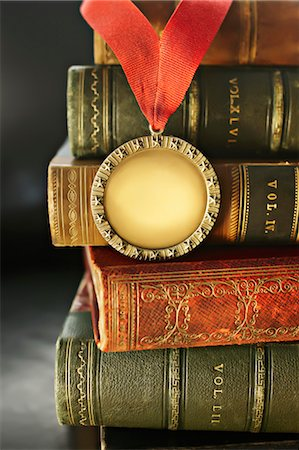 Close-up of Golden Medal with Leather Bound Books Stock Photo - Rights-Managed, Code: 700-03553432
