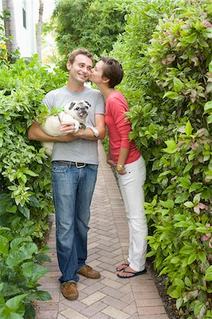 dog kissing man - Portrait of Couple With Pug Stock Photo - Rights-Managed, Code: 700-03596310