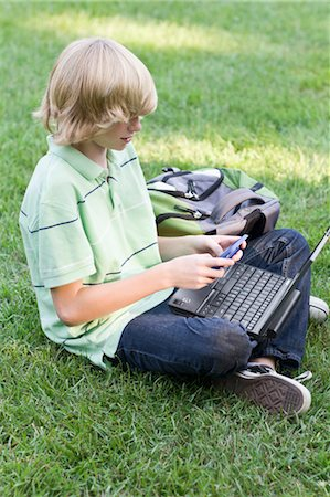 Boy with Laptop and Cell Phone Sitting on Grass Stock Photo - Rights-Managed, Code: 700-03644529