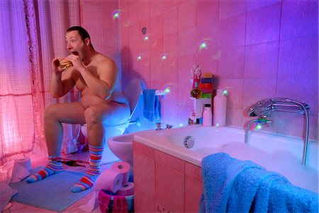 quirky - Nude Man Sitting on Toilet Eating a Sandwich Stock Photo - Rights-Managed, Code: 700-03665637