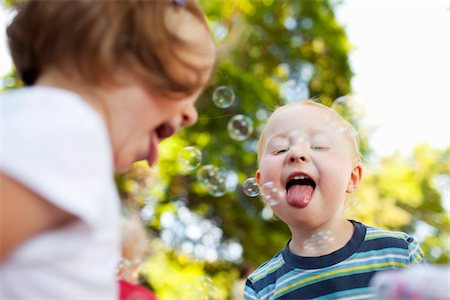 Boy and Girl Catching Bubbles with Tongues Stock Photo - Rights-Managed, Code: 700-03696882
