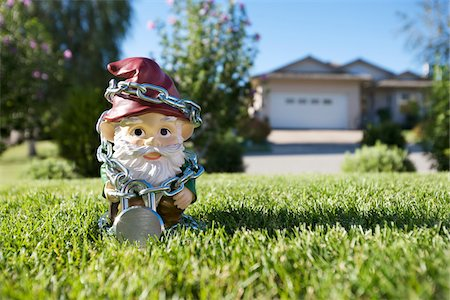 restrained - Gnome on Lawn Tied Up in Chains, Pentiction, Okanagan Valley, British Columbia, Canada Stock Photo - Rights-Managed, Code: 700-03697944