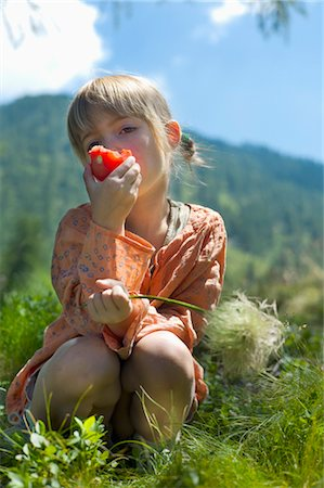 Girl Eating Tomato during Summer Mountain Excursion, Italian Alps, Italy Stock Photo - Rights-Managed, Code: 700-03697947