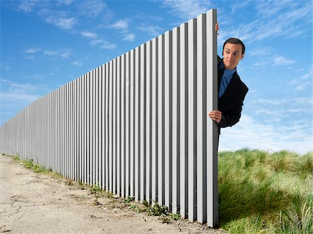 restrained - Businessman Peeking Out from Behind Eternal Fence Stock Photo - Rights-Managed, Code: 700-03698119