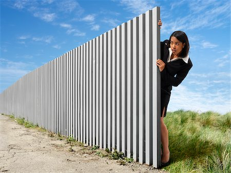 Businesswoman Peeking out from Behind Eternal Fence Foto de stock - Con derechos protegidos, Código: 700-03698120