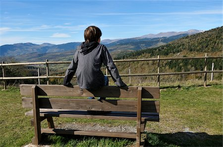 rear - Boy Sitting on Bench and Looking at Landscape Stock Photo - Rights-Managed, Code: 700-03698235