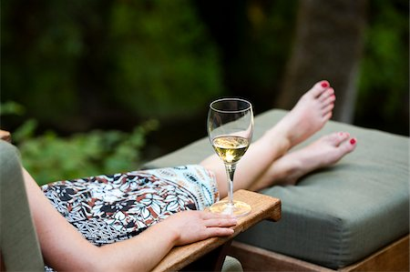 Woman Relaxing on Lounge Chair with Glass of Wine Stock Photo - Rights-Managed, Code: 700-03719289