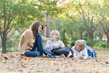 Mother Reading with Sons Outdoors Stock Photo - Rights-Managed, Code: 700-03719341