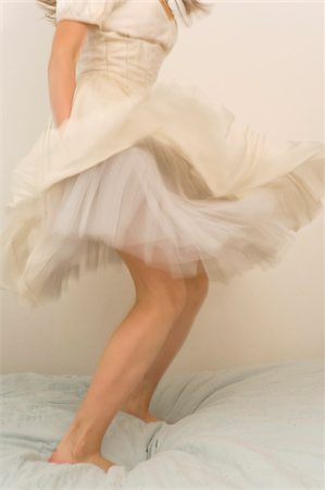 Girl Wearing Dress and Jumping on Bed Stock Photo - Rights-Managed, Code: 700-03720139