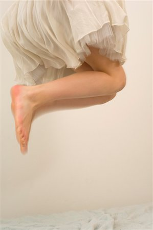 Legs and Skirt of Teenage Girl Jumping on Bed Stock Photo - Rights-Managed, Code: 700-03720140