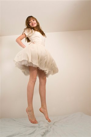 Teenage Girl Jumping on Bed Stock Photo - Rights-Managed, Code: 700-03720141