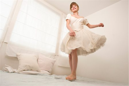 Teenage Girl Jumping on Bed Stock Photo - Rights-Managed, Code: 700-03720142