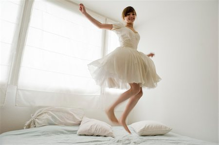 Young girl, teenager, having fun, jumping on bed in her white ballarina dress, in front of window, Salzburg, Austria, MR yes, PR no, Stock Photo - Rights-Managed, Code: 700-03720143