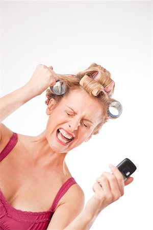 Frustrated Woman with Cell Phone and Curlers in Hair Stock Photo - Rights-Managed, Code: 700-03738101