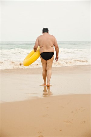 fat man full body - Man Carrying Inflatable Ring on Beach Stock Photo - Rights-Managed, Code: 700-03739473