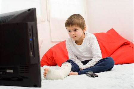 Boy with Cast on Leg Watching TV Stock Photo - Rights-Managed, Code: 700-03777768