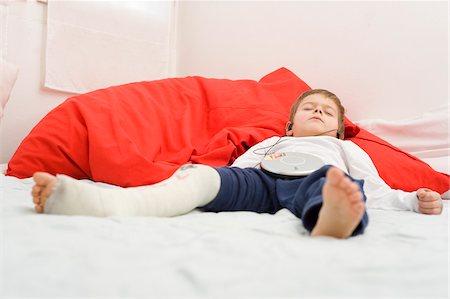 Boy with Broken Leg Wearing Earphones Stock Photo - Rights-Managed, Code: 700-03777775