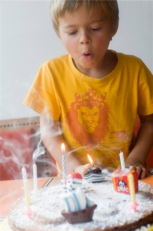 Boy Blowing out Candles on Birthday Cake Stock Photo - Rights-Managed, Code: 700-03777788