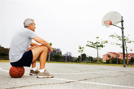 Man Sitting on Basketball on Basketball Court Stock Photo - Rights-Managed, Code: 700-03784263