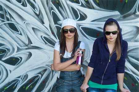 Young Girls Holding Can of Spray Paint in front of Graffiti Covered Wall Stock Photo - Rights-Managed, Code: 700-03787572