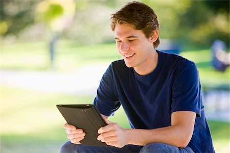 Man Using iPad in Park Stock Photo - Rights-Managed, Code: 700-03799532