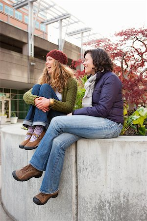 Two Women Laughing and Sitting on Cement Wall Stock Photo - Rights-Managed, Code: 700-03815020
