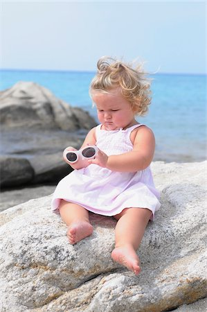 Little Girl with Sunglasses Sitting on Rock Stock Photo - Rights-Managed, Code: 700-03836230