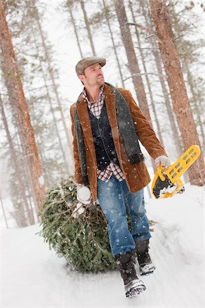 snow christmas tree white - Man with Chainsaw Dragging Christmas Tree Stock Photo - Rights-Managed, Code: 700-03849328