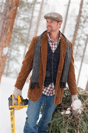 snow christmas tree white - Man with Chainsaw Dragging Fresh Cut Tree Stock Photo - Rights-Managed, Code: 700-03849329