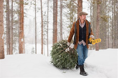 snow christmas tree white - Man with Chainsaw Dragging Tree Stock Photo - Rights-Managed, Code: 700-03849330