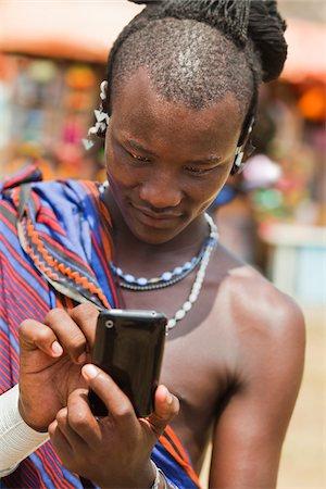 Masai Man in Traditional Dress Using Cell Phone, Zanzibar, Tanzania Stock Photo - Rights-Managed, Code: 700-03907391