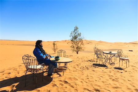 Man Sitting on Chair at Table in Desert, Erg Chebbi, Morocco Stock Photo - Rights-Managed, Code: 700-03958220