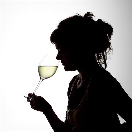 Silhouette Portrait of a young woman enjoying a glass of white wine Stock Photo - Rights-Managed, Code: 824-06492124