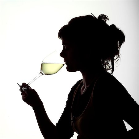 Silhouette portrait of a young girl tasting a glass of white wine Stock Photo - Rights-Managed, Code: 824-06492125