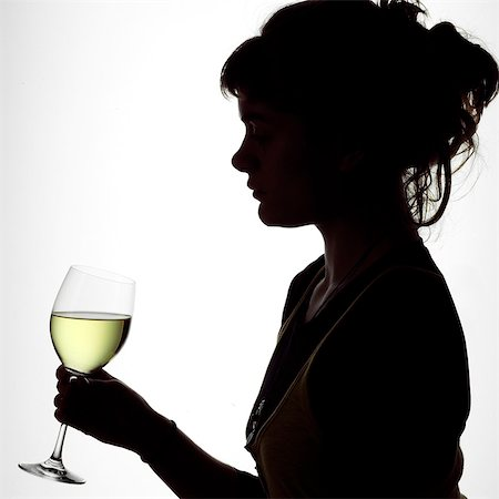 Silhouette Portrait of a young woman enjoying a glass of white wine Stock Photo - Rights-Managed, Code: 824-06492121