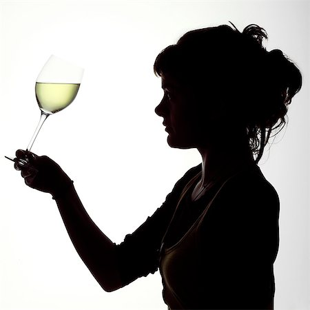 Silhouette Portrait of a young woman enjoying a glass of white wine Stock Photo - Rights-Managed, Code: 824-06492122