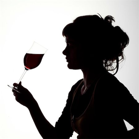 Silhouette portrait of a young woman enjoying a glass of red wine Stock Photo - Rights-Managed, Code: 824-06492132