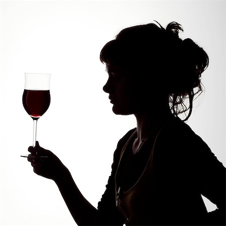 Silhouette portrait of a young woman enjoying a glass of red wine Stock Photo - Rights-Managed, Code: 824-06492133