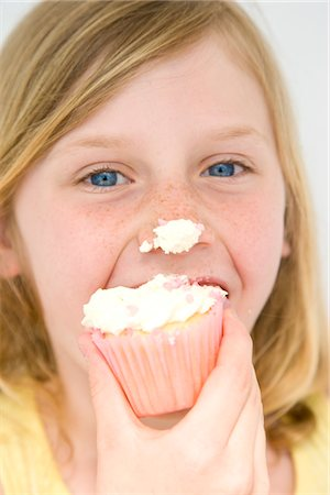 Young Girl Biting Cupcake with Icing on Nose Stock Photo - Rights-Managed, Code: 822-05554345