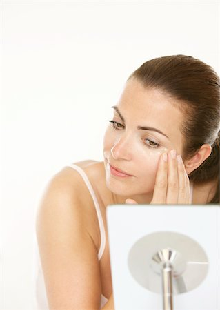personal care - Woman Looking into the Mirror Applying Eye Cream Stock Photo - Rights-Managed, Code: 822-05554602