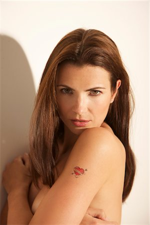 forever - Woman Looking Over Shoulder with Hearth Shape Tattoo on Arm Stock Photo - Rights-Managed, Code: 822-05554704