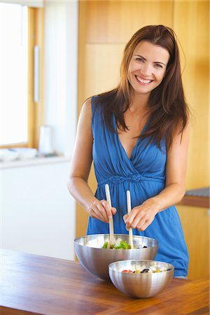 Smiling Woman Tossing Salad Stock Photo - Rights-Managed, Code: 822-05554730