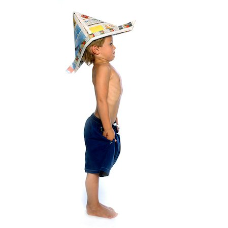 Boy Wearing Newspaper Hat Standing Straight and Stiff, Side View Stock Photo - Rights-Managed, Code: 822-05554797