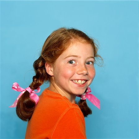 preteen girl pigtails - Smiling Girl Looking Over Shoulder Stock Photo - Rights-Managed, Code: 822-05554799