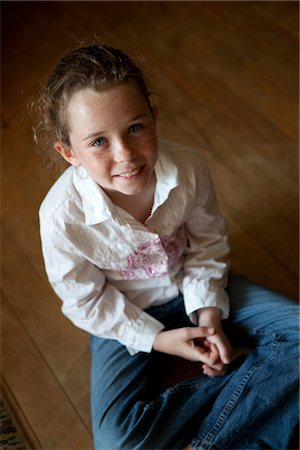 Smiling Girl Sitting on Wood Flooring Stock Photo - Rights-Managed, Code: 822-05554827