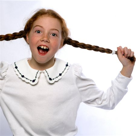 preteen girl pigtails - Smiling Girl with Mouth Open Pulling her Braids Stock Photo - Rights-Managed, Code: 822-05554861