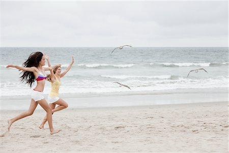 Teenage Girls Chasing Birds on Beach Stock Photo - Rights-Managed, Code: 822-05554871
