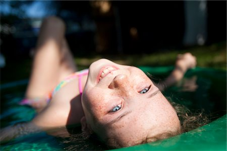 preteen girl swimsuit - Smiling Girl Lying in Paddling Pool, Close-up view Stock Photo - Rights-Managed, Code: 822-05554938