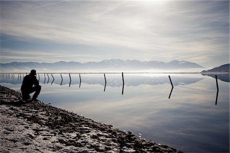 panoramic winter scene - Man Crouching on Lakeshore Admiring Mountain View Stock Photo - Rights-Managed, Code: 822-05554983