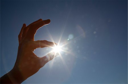 fingers holding - Man's Hand with Sun Between Fingertips Stock Photo - Rights-Managed, Code: 822-05554996